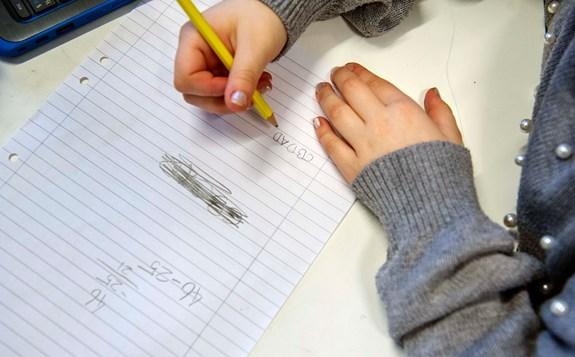 elev skriver på papper
